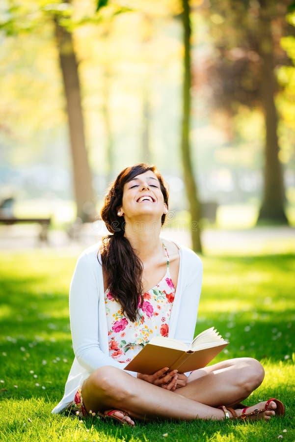 Livro de leitura da mulher e divertimento ter no parque foto de stock