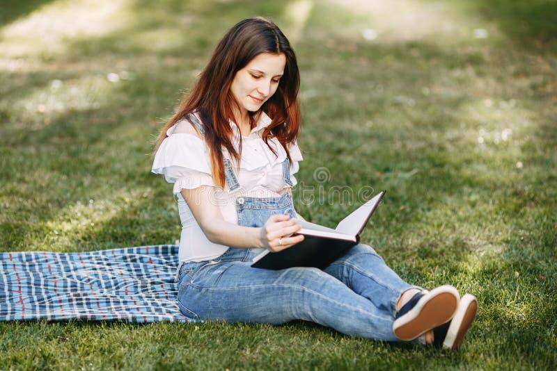 Livro de leitura da mulher gravida a seu bebê por nascer fotografia de stock royalty free