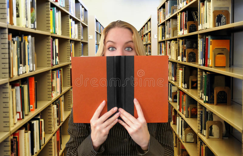 Livro De Leitura Da Mulher Na Biblioteca Foto de Stock
