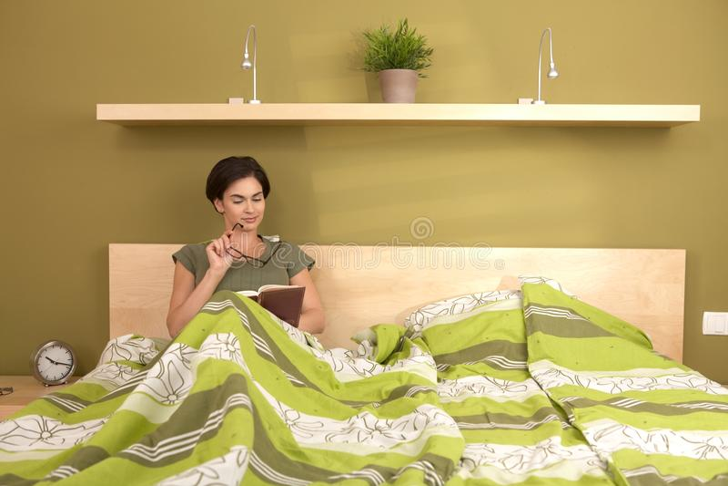 Livro de leitura da mulher na cama imagens de stock royalty free