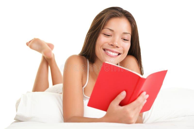 Livro de leitura da mulher na cama foto de stock