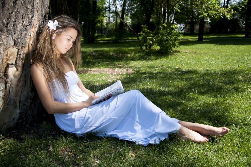 Livro de leitura da mulher nova no parque imagem de stock