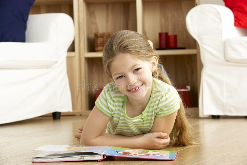 Livro de leitura da rapariga em casa imagem de stock royalty free