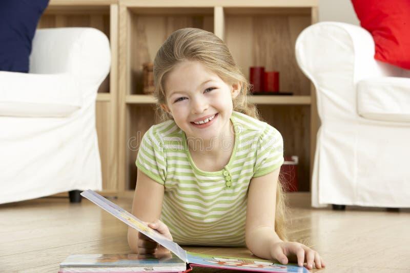 Livro de leitura da rapariga em casa fotos de stock royalty free