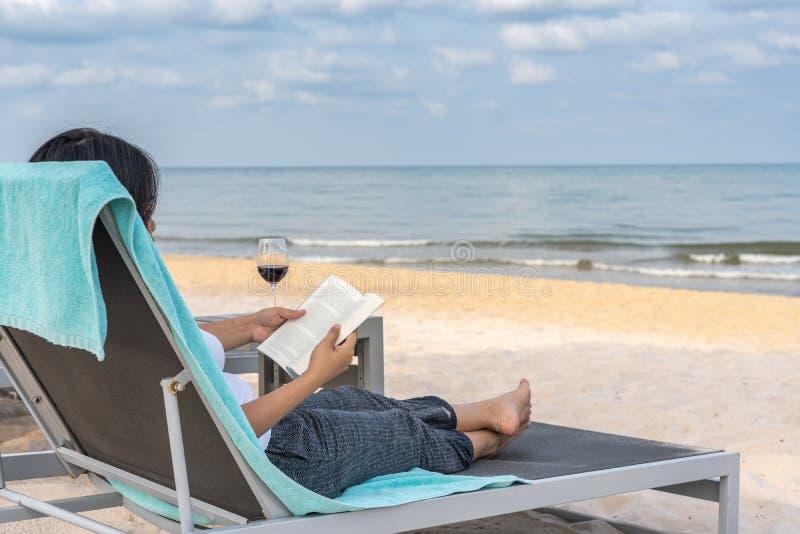 Livro de leitura da senhora e para relaxar na praia do ver?o fotografia de stock royalty free