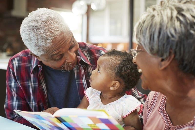 Livro de leitura das avós com neta do bebê em casa imagens de stock