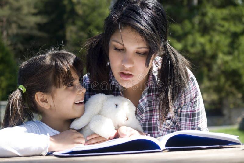 Livro de leitura das irmãs junto imagem de stock