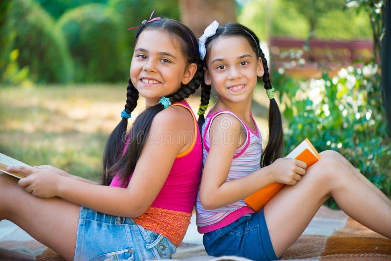 Livro de leitura das irmãs no parque do verão imagens de stock royalty free