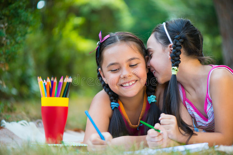 Livro de leitura das irmãs no parque do verão fotografia de stock