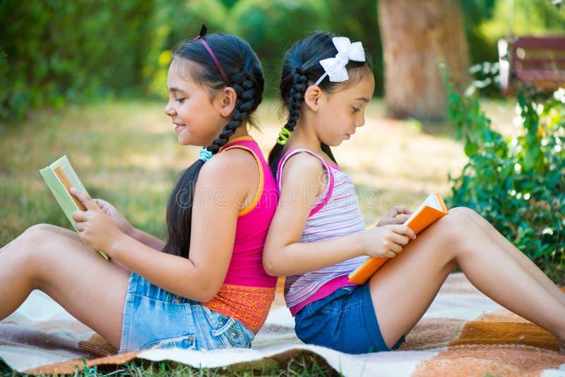 Livro de leitura das irmãs no parque do verão fotografia de stock royalty free