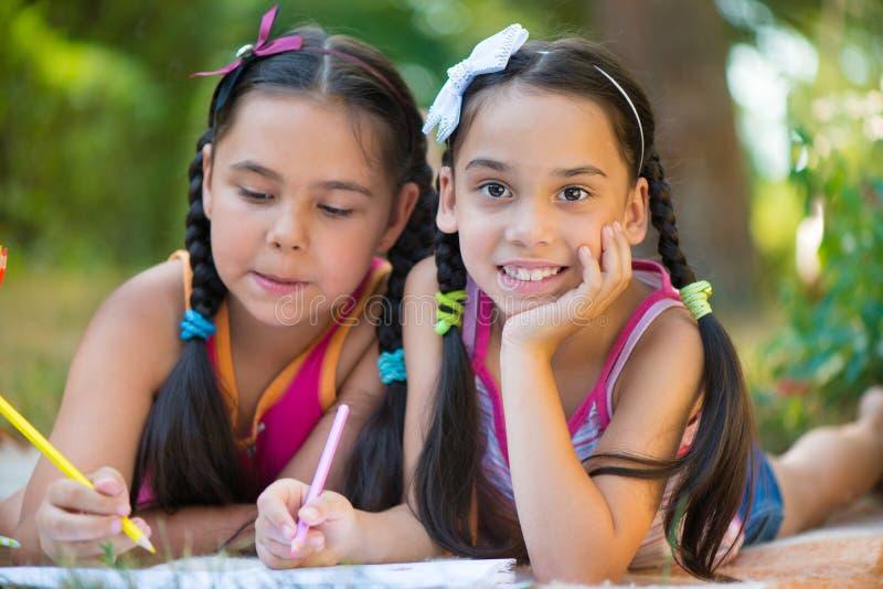 Livro de leitura das irmãs no parque do verão imagens de stock