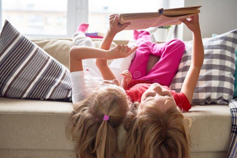 Livro de leitura das meninas em casa fotografia de stock
