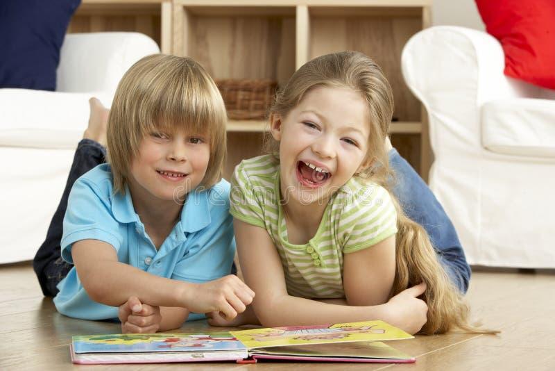 Livro de leitura de duas crianças novas em casa imagens de stock