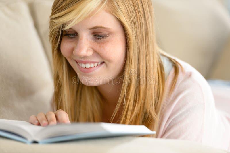 Livro de leitura de sorriso do adolescente do estudante no sofá imagem de stock royalty free