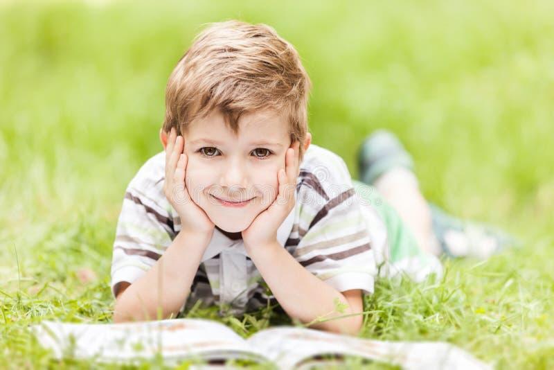 Livro de leitura de sorriso do menino ao ar livre foto de stock