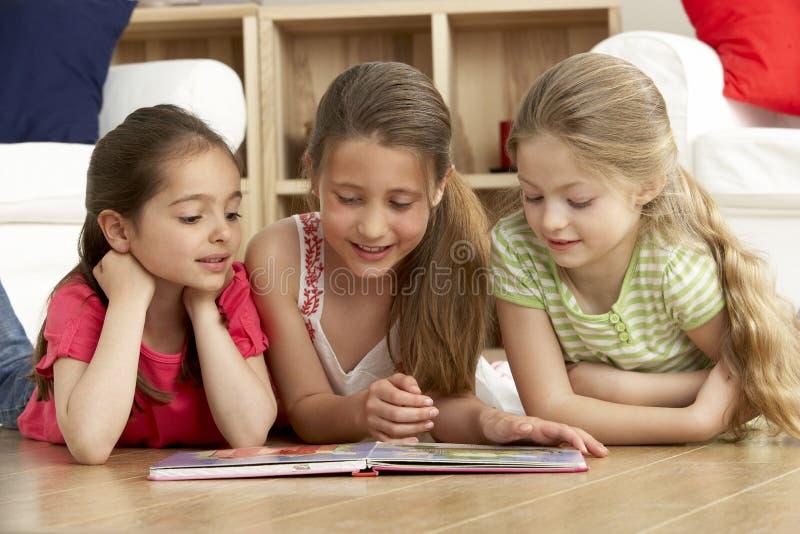 Livro de leitura de três raparigas em casa imagens de stock