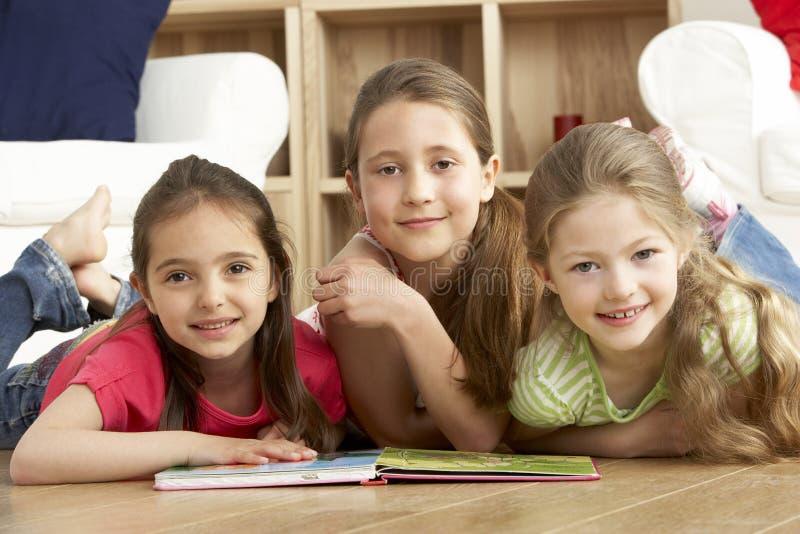 Livro de leitura de três raparigas em casa foto de stock royalty free