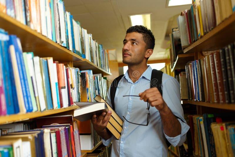 Livro de leitura do estudante entre as prateleiras na biblioteca fotografia de stock royalty free