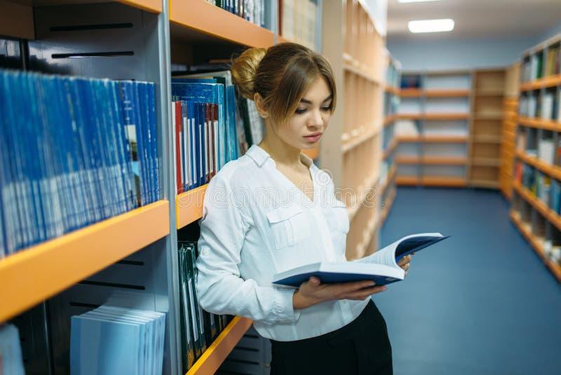 Livro de leitura do estudante fêmea na estante, biblioteca imagem de stock