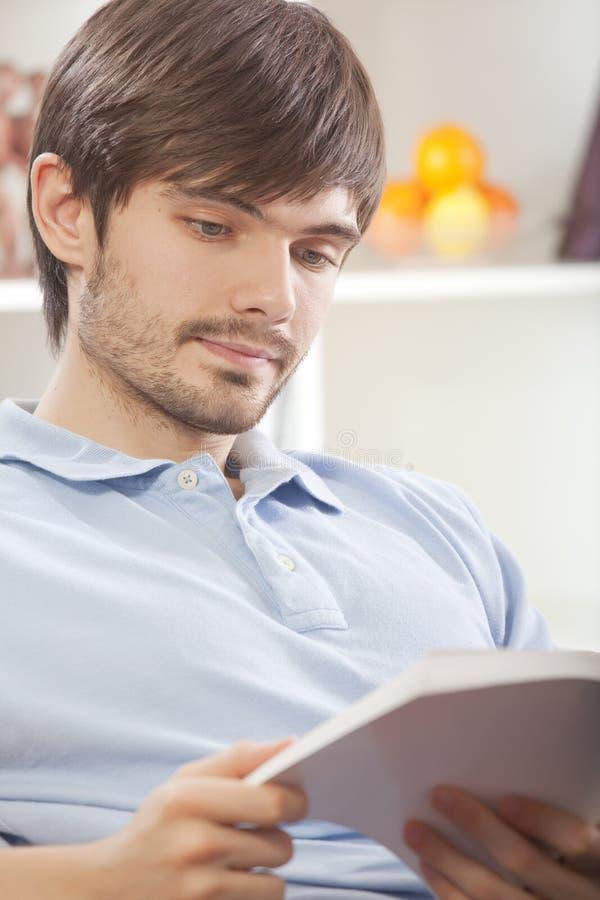 Livro de leitura do homem em casa fotografia de stock royalty free