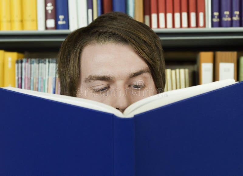 Livro de leitura do homem novo na biblioteca fotografia de stock