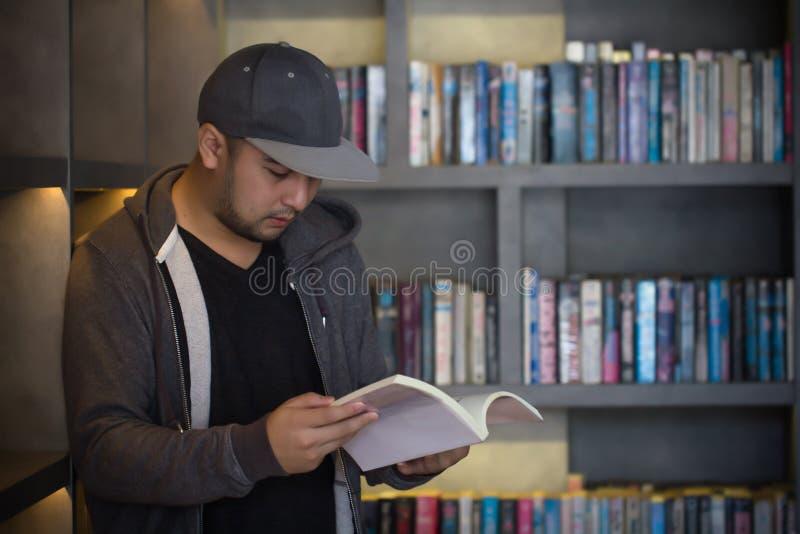 Livro de leitura do homem novo na biblioteca r : fotografia de stock royalty free