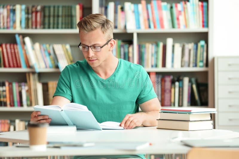 Livro de leitura do homem novo na tabela fotografia de stock royalty free
