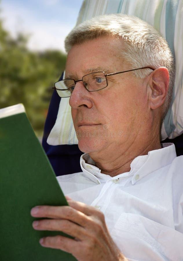 Livro de leitura do homem sênior foto de stock