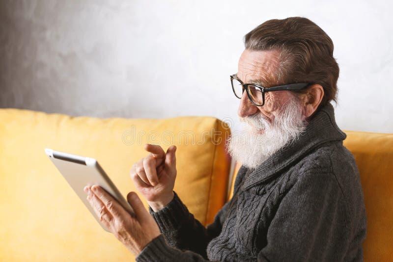 Livro de leitura do homem superior na tabuleta de Digitas imagens de stock royalty free