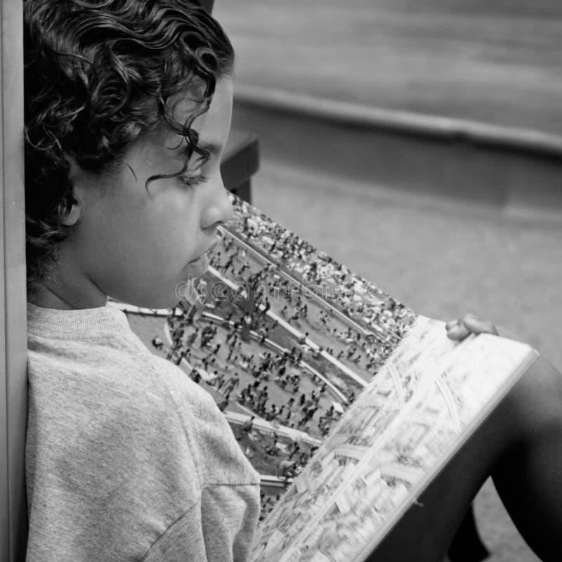 Livro de leitura do menino imagens de stock