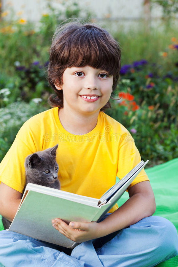 Livro de leitura do menino com o gatinho na jarda, criança com leitura do animal de estimação imagem de stock royalty free