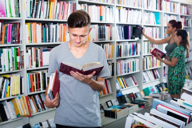 Livro de leitura do menino do adolescente na loja imagens de stock royalty free