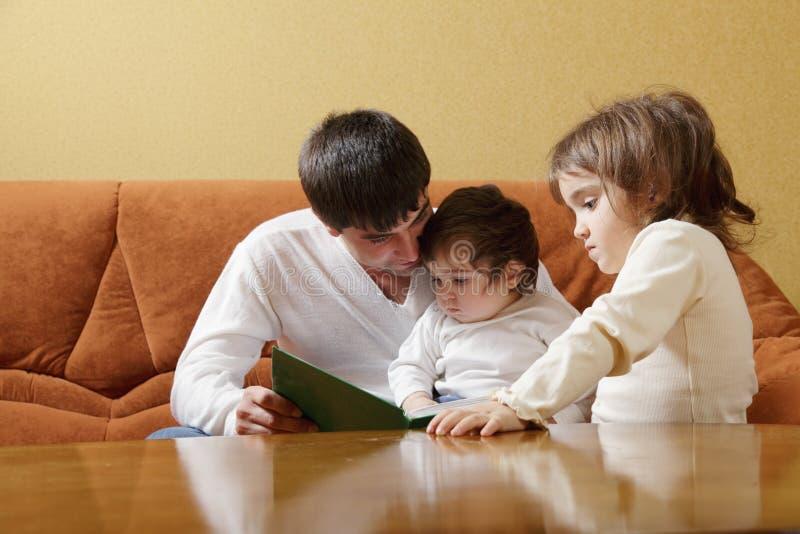Livro de leitura do pai às filhas fotografia de stock