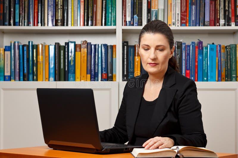 Livro de leitura do portátil do escritório da mulher imagens de stock