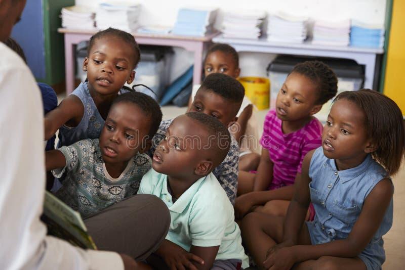 Livro de leitura do professor aos alunos elementares na classe imagens de stock royalty free