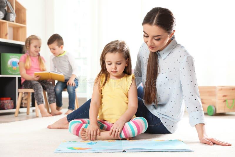 Livro de leitura do professor de jardim de infância à criança Aprendizagem e jogo fotos de stock royalty free