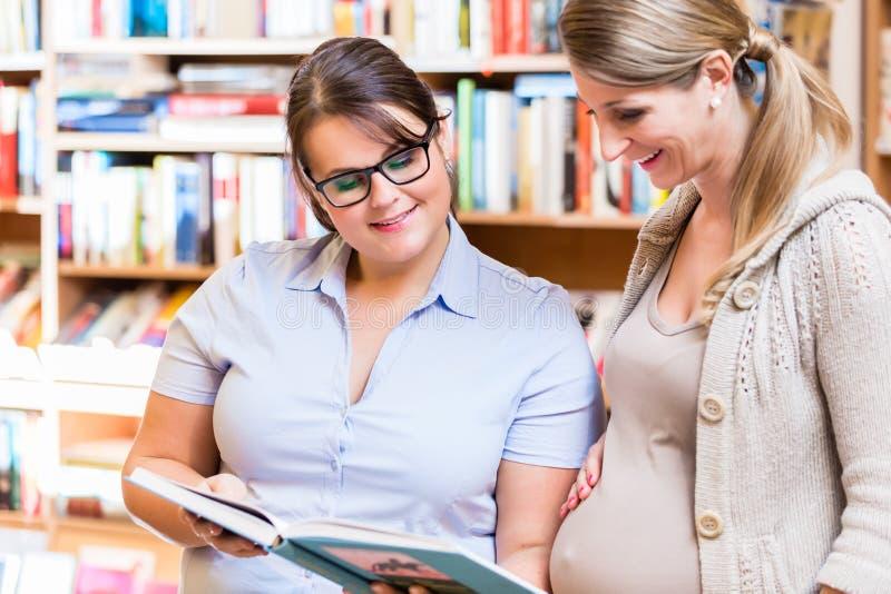 Livro de leitura de dois amigos na livraria junto imagens de stock