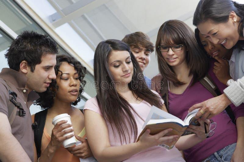 Livro de leitura dos estudantes com professor fotografia de stock royalty free