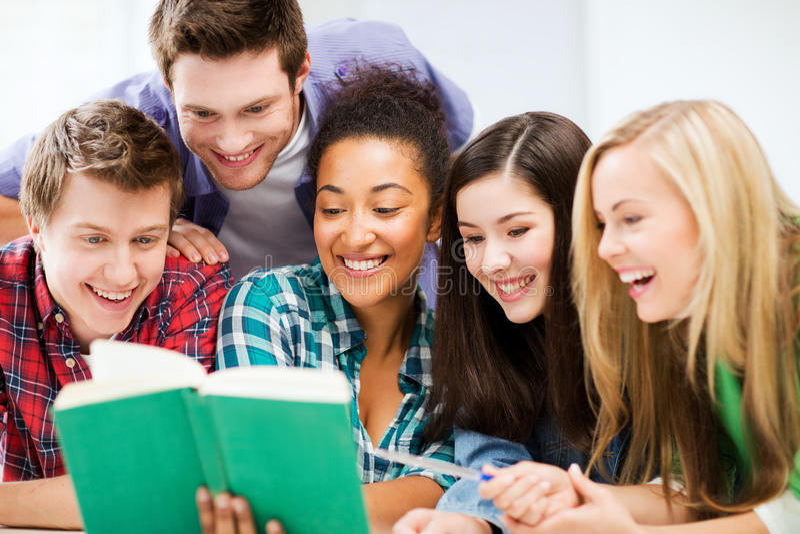 Livro de leitura dos estudantes na escola imagens de stock