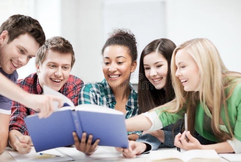 Livro de leitura dos estudantes na escola fotografia de stock