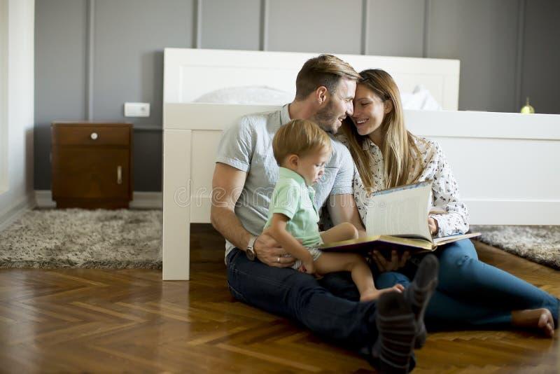 Livro de leitura dos pais ao rapaz pequeno e para ter o divertimento no assoalho fotos de stock royalty free
