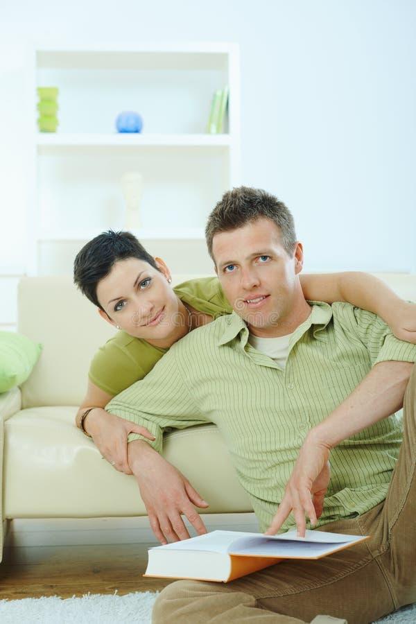 Livro de leitura dos pares em casa fotos de stock royalty free