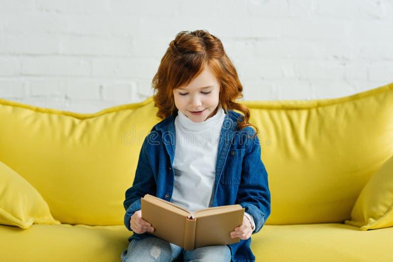 Livro de leitura entusiástico da criança pequena fotografia de stock