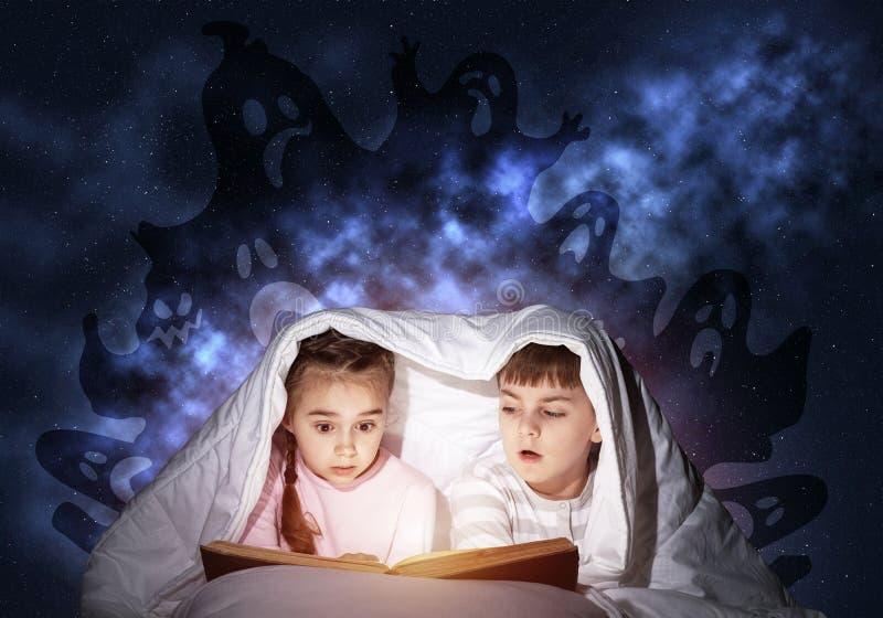 Livro de leitura entusiástico da menina e do menino foto de stock royalty free