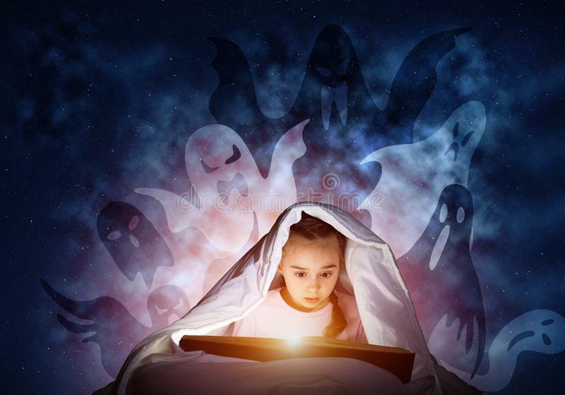Livro de leitura entusiástico da menina na cama fotografia de stock royalty free