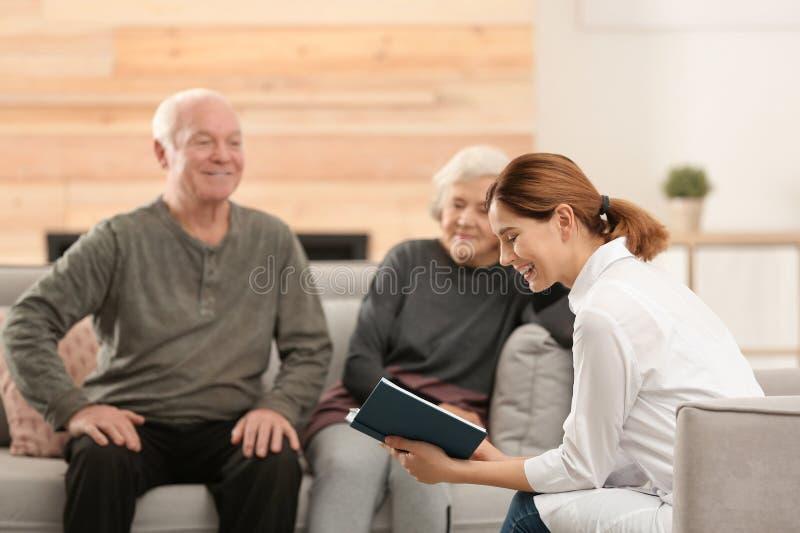 Livro de leitura fêmea do cuidador aos esposos idosos foto de stock