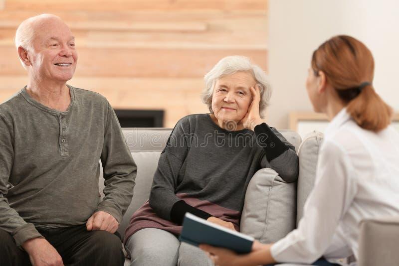 Livro de leitura fêmea do cuidador aos esposos idosos fotos de stock royalty free