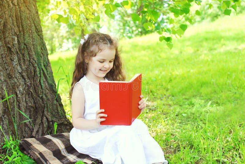 Livro de leitura feliz da criança na grama no verão imagem de stock