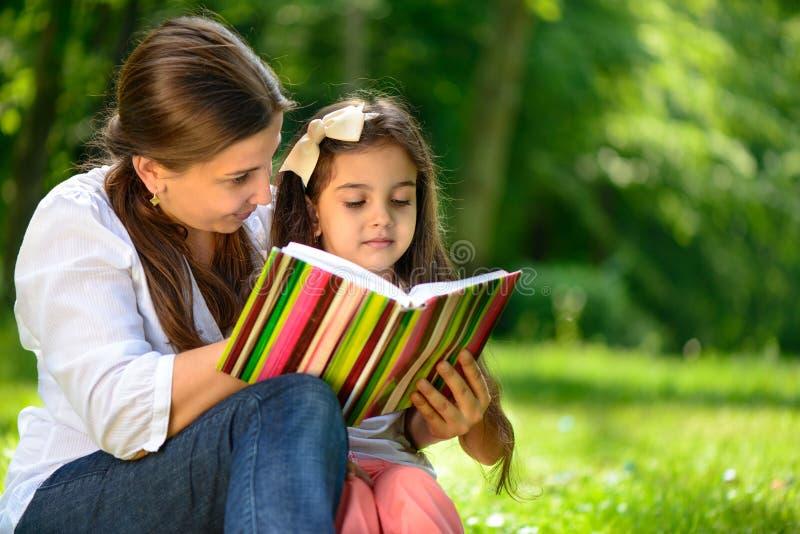 Livro de leitura feliz da família do latino imagem de stock