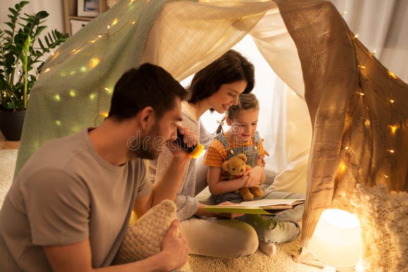 Livro de leitura feliz da família na barraca das crianças em casa imagens de stock